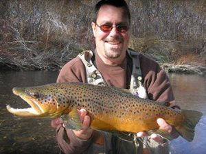 The author is holding a large brown trout