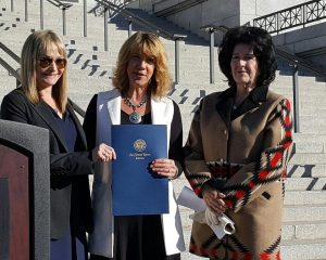 Dr. Laura Nelson presents Tammie Cooper and Robin Erikson with the Governor's Declaration for Alternative Fuel Vehicle Month
