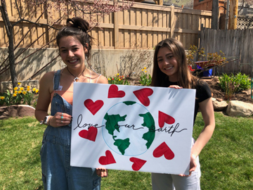 Two sisters holding a poster with the earth and hearts.