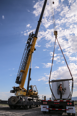 Picture of a crane lifting a new air quality monitor into place.
