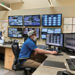 photograph of a water operator wearing a face mask at a desk looking at computer monitors.