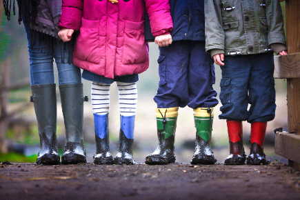 kids standing in a row with muddy rain boots on
