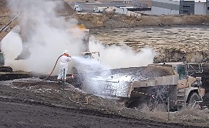A person in a hazmat suit blowing chemicals from a hose onto the soil in a dump truck. A backhoe and steam are in the background.